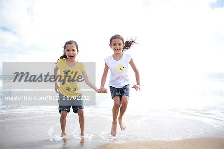 Twin Girls Jumping Over Waves Stock Photo - Rights-Managed, Image code: 822-06702212
