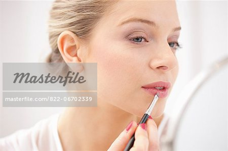 Woman Applying Lipstick with Makeup Brush Stock Photo - Rights-Managed, Image code: 822-06702339