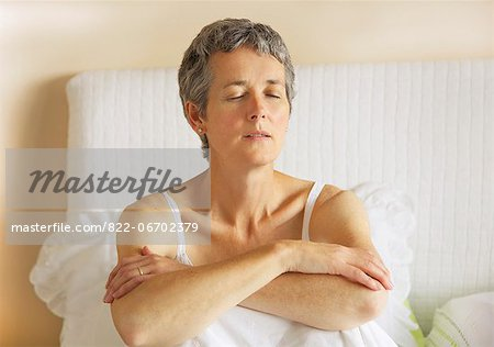 Woman Sitting in Bed with Arms Crossed Stock Photo - Rights-Managed, Image code: 822-06702379