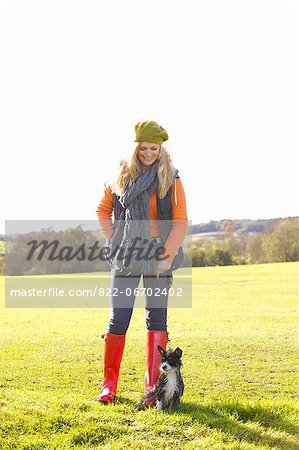 Woman Standing in Park with Dog Stock Photo - Rights-Managed, Image code: 822-06702402