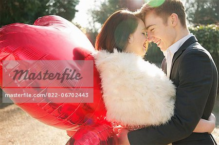 Young Couple Embracing Holding Heart Shaped Balloons Stock Photo - Rights-Managed, Image code: 822-06702443
