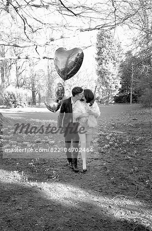 Young Couple Kissing in Park Holding Heart Shaped Balloons Stock Photo - Rights-Managed, Image code: 822-06702464