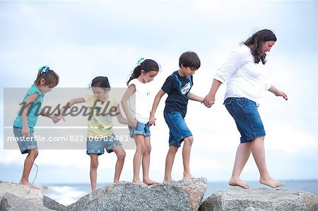 Family Walking on Rocks by Sea Holding Hands Stock Photo - Rights-Managed, Image code: 822-06702483