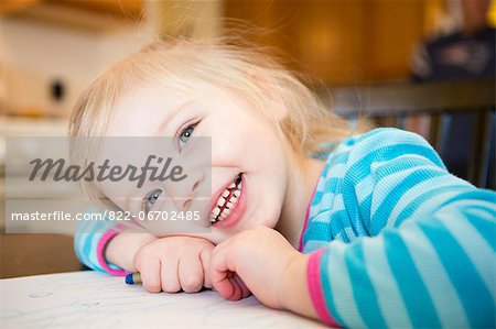 Smiling Girl Resting Head on Table Stock Photo - Rights-Managed, Image code: 822-06702485