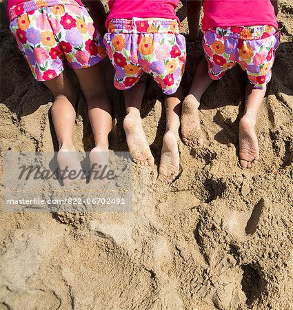 Back View of Girls in Matching Outfit Kneeling on Sand, Cropped Stock Photo - Rights-Managed, Image code: 822-06702491