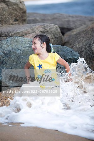 Girl Sitting on Rocks Playing in Sea Waves Stock Photo - Rights-Managed, Image code: 822-06702528