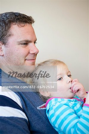 Girl Sucking Thumb on Father Lap Stock Photo - Rights-Managed, Image code: 822-06702534
