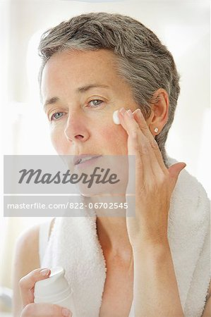 Woman Applying Moisturizing Cream on Face Stock Photo - Rights-Managed, Image code: 822-06702545