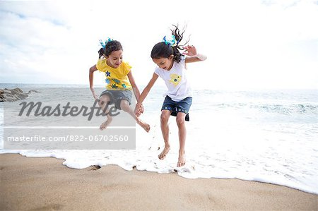 Twin Girls Jumping Over Waves Stock Photo - Rights-Managed, Image code: 822-06702560