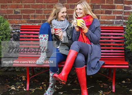 Mother and Daughter Sitting on Red Bench with Hot Drinks Stock Photo - Rights-Managed, Image code: 822-06702574