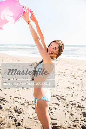 Woman on Beach with Arms Outstretched Holding T-shirt Stock Photo - Rights-Managed, Image code: 822-07117313