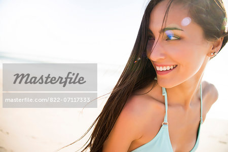 Smiling Young Woman Looking Over Shoulder Stock Photo - Rights-Managed, Image code: 822-07117333