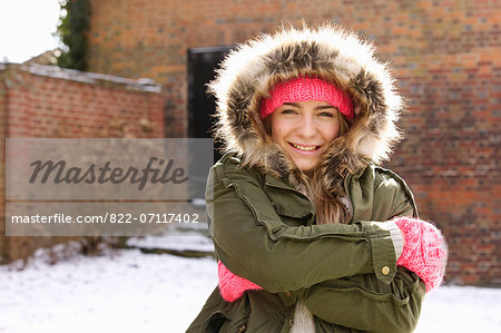Smiling Teenage Girl Wearing Parka Hugging Herself Outdoors Stock Photo - Rights-Managed, Image code: 822-07117402