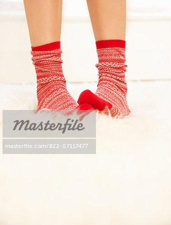 Woman's Feet with Red and White Wool Socks on Fluffy Rug Stock Photo - Rights-Managed, Image code: 822-07117477