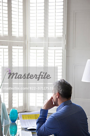 Man Sitting at Desk Looking Over Document Stock Photo - Rights-Managed, Image code: 822-07117535