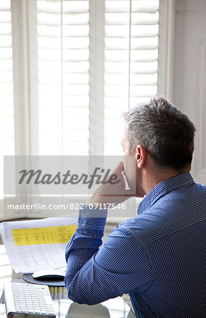 Man Sitting at Desk Looking Over Document Stock Photo - Rights-Managed, Image code: 822-07117546