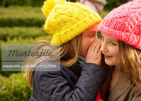 Young Girl Whispering in Friend's Ear Stock Photo - Rights-Managed, Image code: 822-07117550