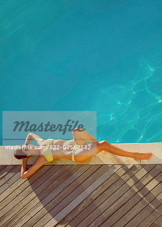 Woman Sunbathing by Swimming Pool, High Angle View Stock Photo - Rights-Managed, Image code: 822-07562582