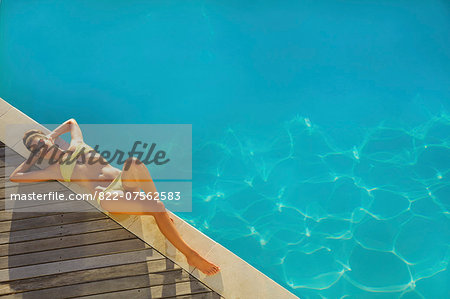 Woman Sunbathing by Swimming Pool, High Angle View Stock Photo - Rights-Managed, Image code: 822-07562583