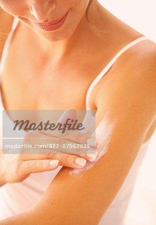 Woman Applying Body Lotion on Arm Stock Photo - Rights-Managed, Image code: 822-07562625