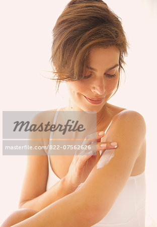 Woman Applying Body Lotion on Arm Stock Photo - Rights-Managed, Image code: 822-07562626
