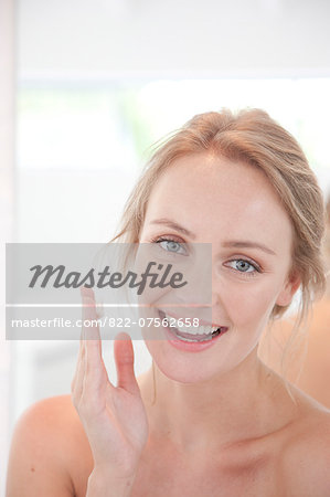 Smiling Woman with Moisturizing Cream on Hand Stock Photo - Rights-Managed, Image code: 822-07562658