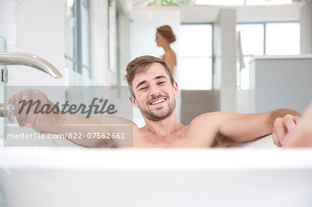 Smiling Man in Bathtub, Woman in Background Stock Photo - Rights-Managed, Image code: 822-07562661