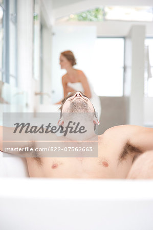 Man Relaxing in Bathtub, Woman in Background Stock Photo - Rights-Managed, Image code: 822-07562663