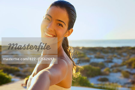 Smiling Young Woman with Arm Raised, Close-up View Stock Photo - Rights-Managed, Image code: 822-07562697