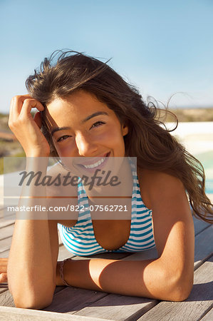 Smiling Young Woman Sunbathing on Deck Stock Photo - Rights-Managed, Image code: 822-07562721