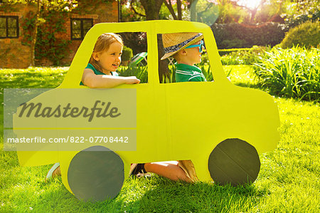 Boy and Girl Kneeling behind Cardboard Cut Out in Shape of Car Stock Photo - Rights-Managed, Image code: 822-07708442