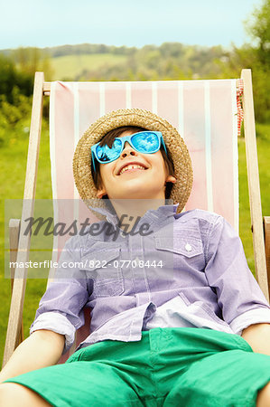 Smiling Boy Wearing Straw Hat and Sunglasses Sitting on Deck Chair Stock Photo - Rights-Managed, Image code: 822-07708444