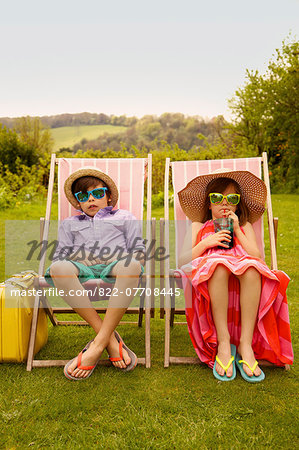 Boy and Girl Wearing Straw Hat and Sunglasses Sitting on Deck Chairs Stock Photo - Rights-Managed, Image code: 822-07708445
