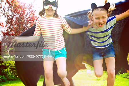 Young Girls Wearing Cape and Mask Running in Garden Stock Photo - Rights-Managed, Image code: 822-07708456