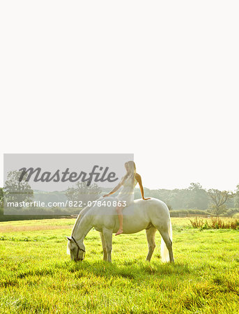 Young Woman Riding Horse in Field Stock Photo - Rights-Managed, Image code: 822-07840863