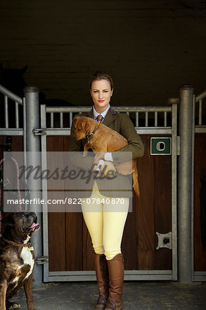 Woman in Riding Outfit Standing in front of Stable Carrying Dog in her Arms Stock Photo - Rights-Managed, Image code: 822-07840870