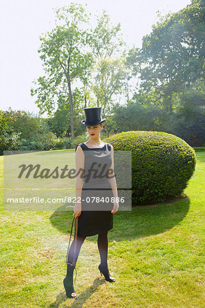 Young Woman in Top Hat and Veil Holding Riding Crop in Garden Stock Photo - Rights-Managed, Image code: 822-07840886