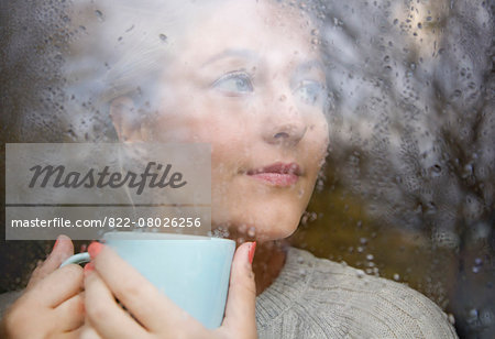 Woman Holding Drinking Cup behind Rainy Window Stock Photo - Rights-Managed, Image code: 822-08026256
