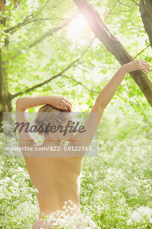 Back View of Nude Woman with Arms Raised In a Meadow Stock Photo - Rights-Managed, Image code: 822-08122364