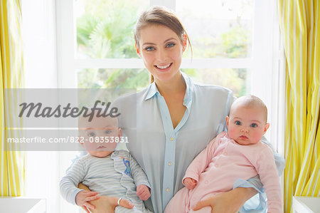 Smiling Mother Holding Twin Babies Stock Photo - Rights-Managed, Image code: 822-08353831