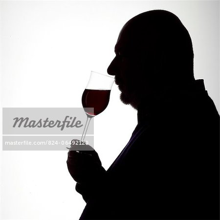 Silhouette Portrait of a Man enjoying a glass of red wine Stock Photo - Rights-Managed, Image code: 824-06492120