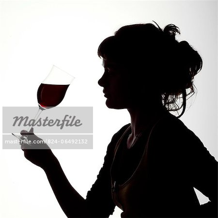 Silhouette portrait of a young woman enjoying a glass of red wine Stock Photo - Rights-Managed, Image code: 824-06492132