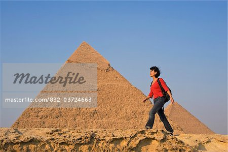Woman with rucksack walking along ancient wall in front of Pyramids Stock Photo - Rights-Managed, Image code: 832-03724663