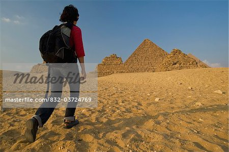 Woman with rucksack walking towards Pyramids at dusk Stock Photo - Rights-Managed, Image code: 832-03724769