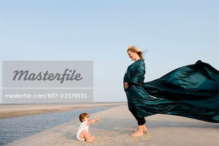 Side profile of a pregnant woman standing on the beach with her baby girl sitting in front of her Stock Photo - Rights-Managed, Image code: 837-02378531
