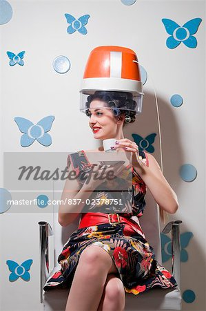Young woman sitting under a hair dryer and drinking tea Stock Photo - Rights-Managed, Image code: 837-02378751