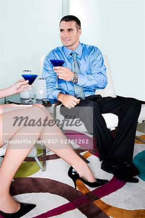 Young man holding a glass of cocktail and looking at a woman sitting beside him Stock Photo - Rights-Managed, Image code: 837-02380202