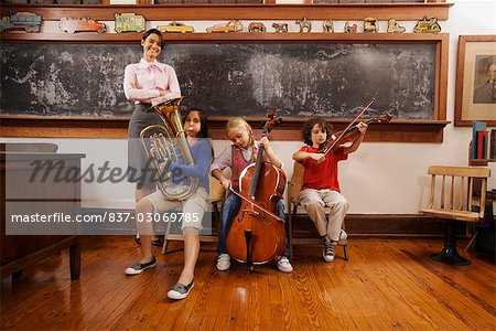 Students playing musical instruments with their teacher standing beside them Stock Photo - Rights-Managed, Image code: 837-03069785