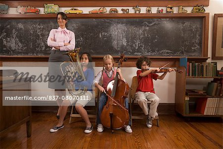 Students playing musical instruments with their teacher standing beside them Stock Photo - Rights-Managed, Image code: 837-03070111