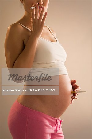Pregnant woman smoking a cigarette Stock Photo - Rights-Managed, Image code: 837-03071452